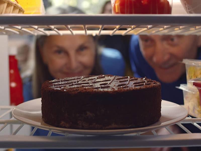 Couple Taking Cake Refrigerator